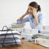 A young businesswoman looking overwhelmed while surrounded by paperwork