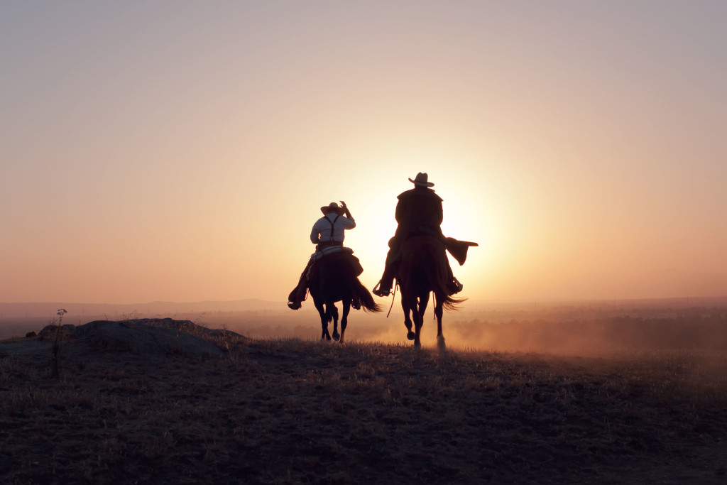 A silhouette of two cowboys riding away from the camera into the sunset in a desert like setting, with one cowboy tipping his hat.